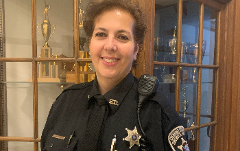 a smiling woman with short hair in police uniform stands in front of trophy case