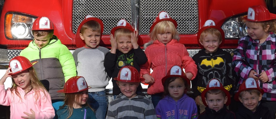 Preschool students in red fire hats in front of a fire truck