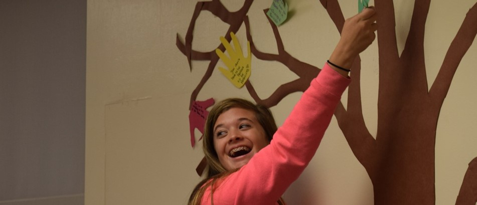 smiling girl in pink jackeet hangs handprint on wall
