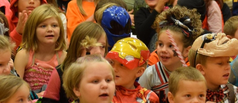 elementary students in Halloween costumes sit on gym floor