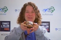A woman in blue shirt and grey jacket smiles as she holds up turtle and stands in front of Buffalo Z