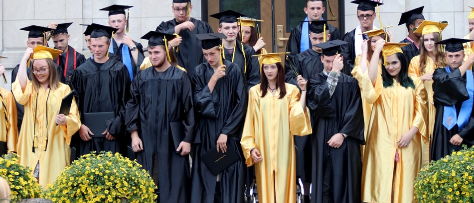 students in graduation gowns and caps stand in front of banner