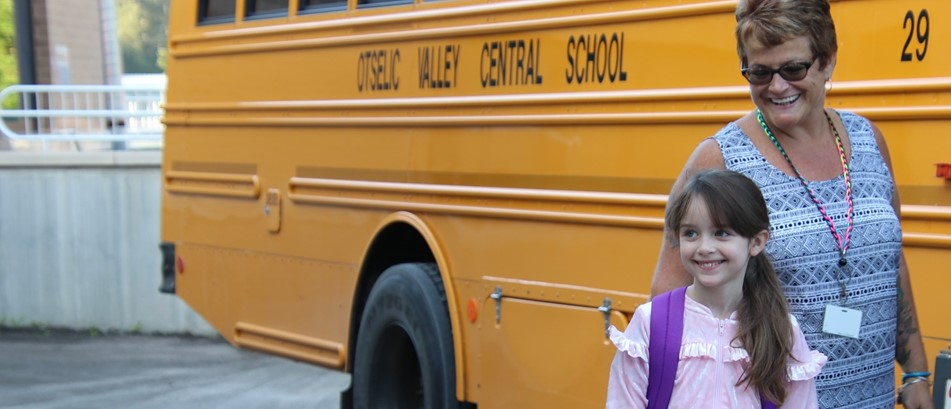 girl in front of school bus with smiling woman behind her