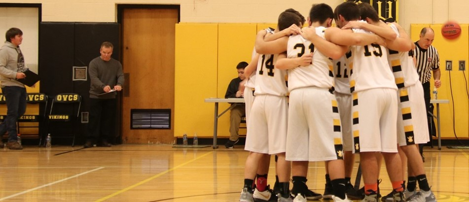 boys basketball team in huddle on gym floor