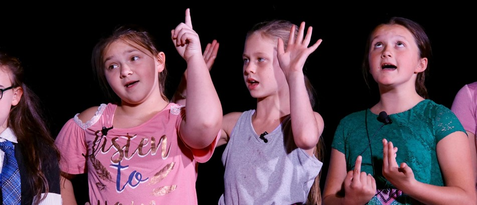 girls with hands in air speak on stage