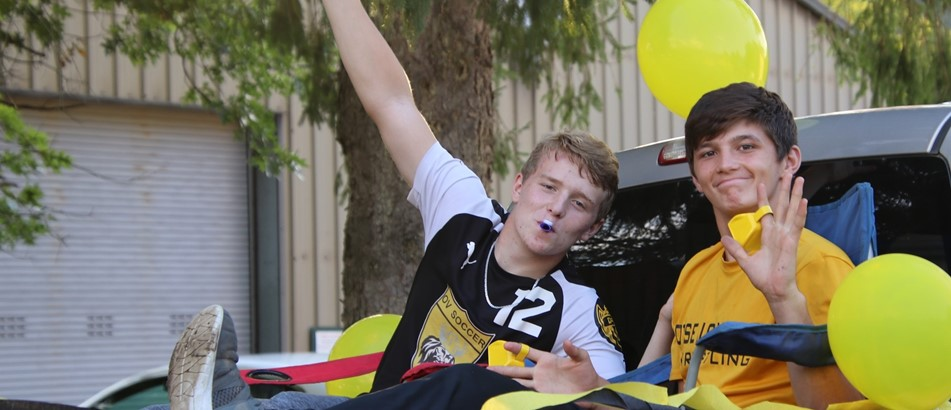 two boys in back of truck with yellow balloons