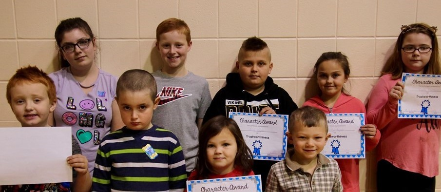 boys and girls hold up certificates