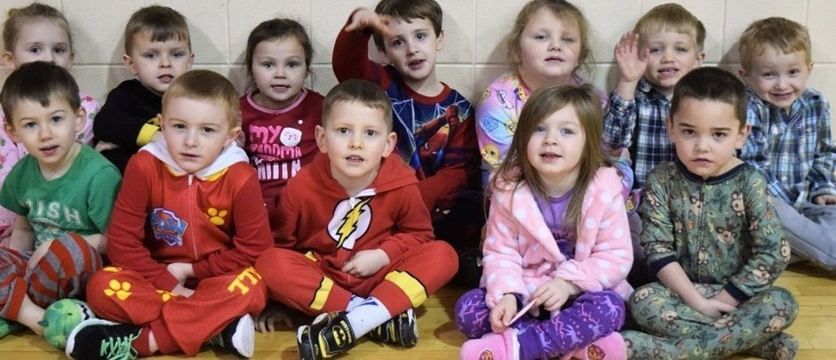 PreK students in pajamas sit and smile