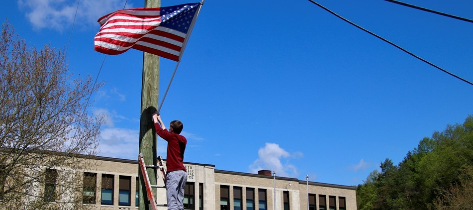 boy in red shirt hangs flag on  pole