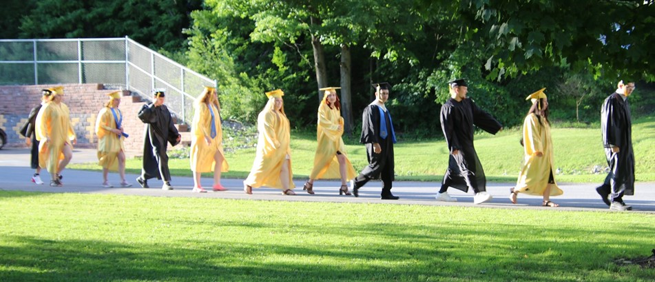 teens in gold and black graduation gowns walk in front of trees