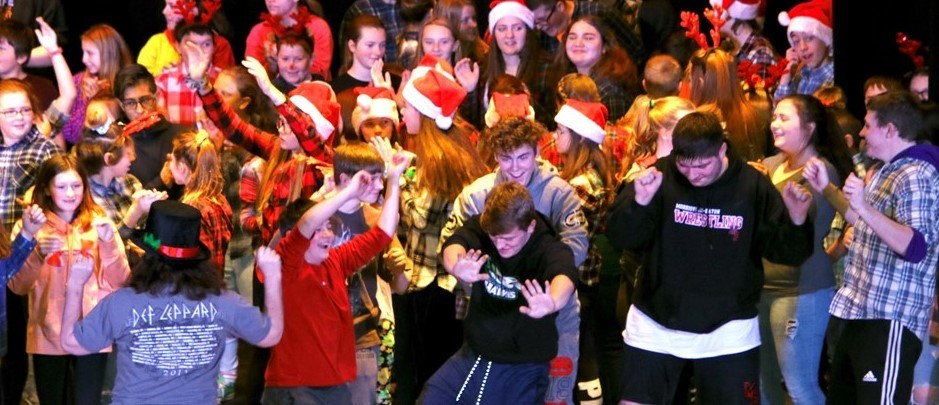 many teenagers, some with red Christmas hats, are dancing with hands in the air
