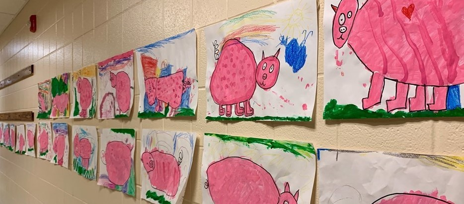 2 rows of children's drawing of pink pigs hang on a long wall