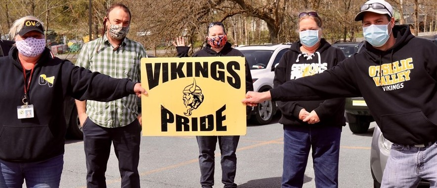 5  adults in face coverings hold gold and black sign that says Vikings Pride