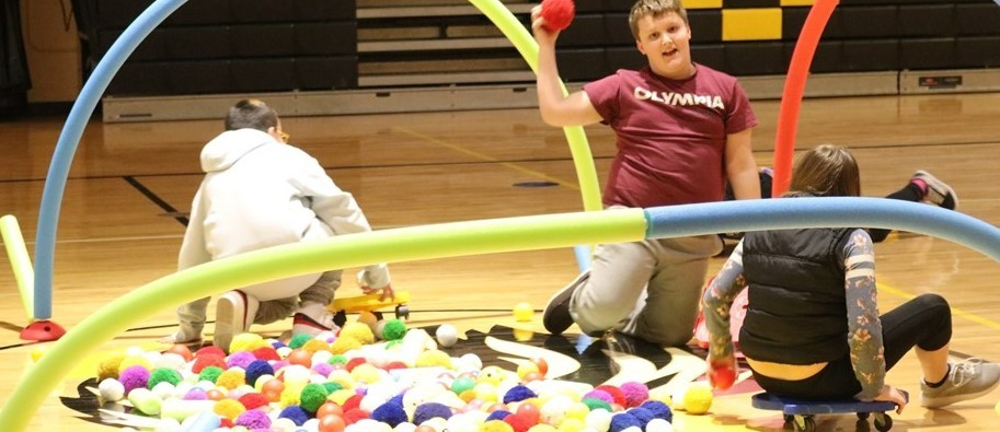 kids plan on gym floor with rubber balls and wheeled scooters