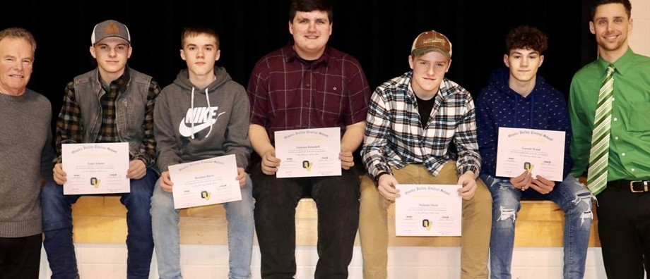 5 teenage boys hold certificates and set on edge of stage, flanked by 2 male coaches