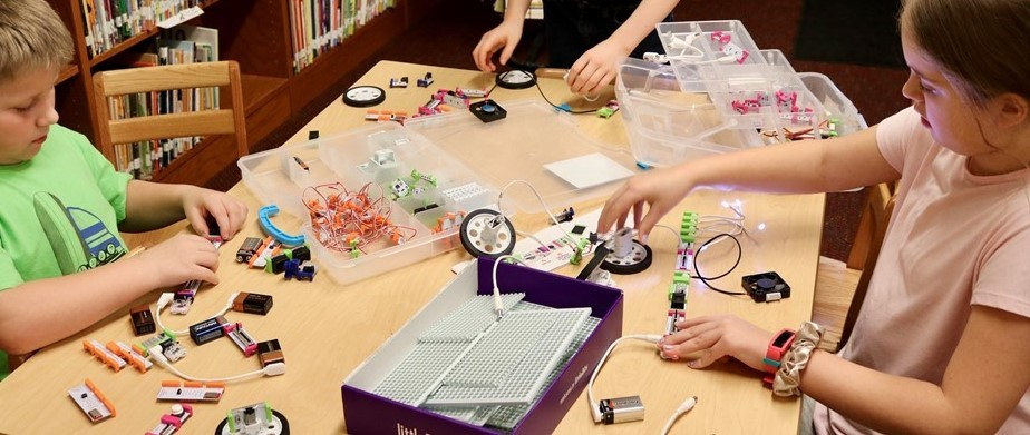 young students work with robotics parts in a library