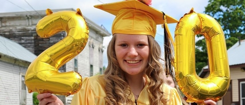 young woman in gold graduation cap holds gold balloons that spell 20