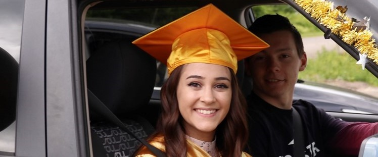 smiling young woman with gold graduation cap seated in car decorated with gold garland