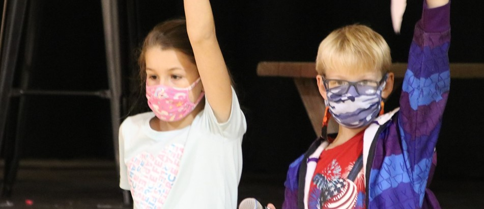 a boy and girl leading Morning Program raise their hands to quiet students as both hold pieces of paper