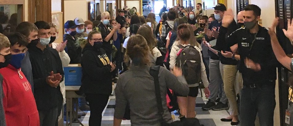 A crowd lines both sides of a high school hallway, cheering on members of the girls soccer team who are exiting the building