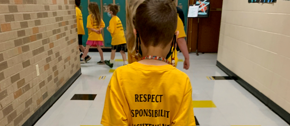 students in matching yellow t-shirts walk down hallway