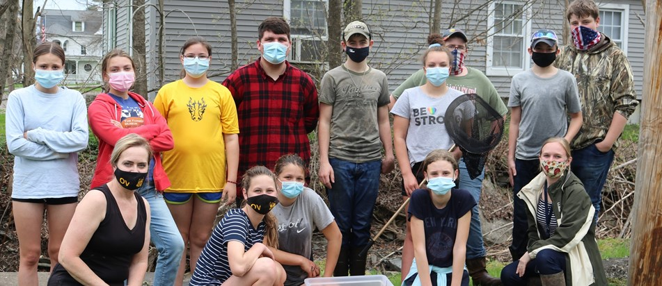 a group of teenagers with two teachers all in masks beside a creek with a bucket of yellow rubber ducks