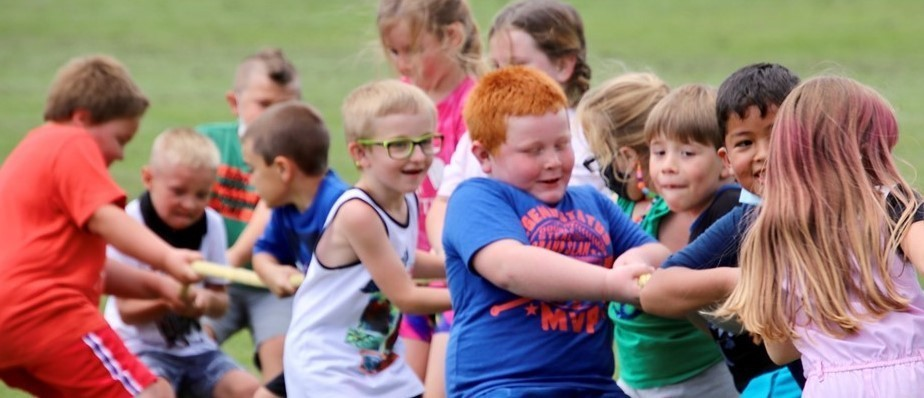 Smiling elementary students in summer clothes pull together on a rope during outdoor tug o'war
