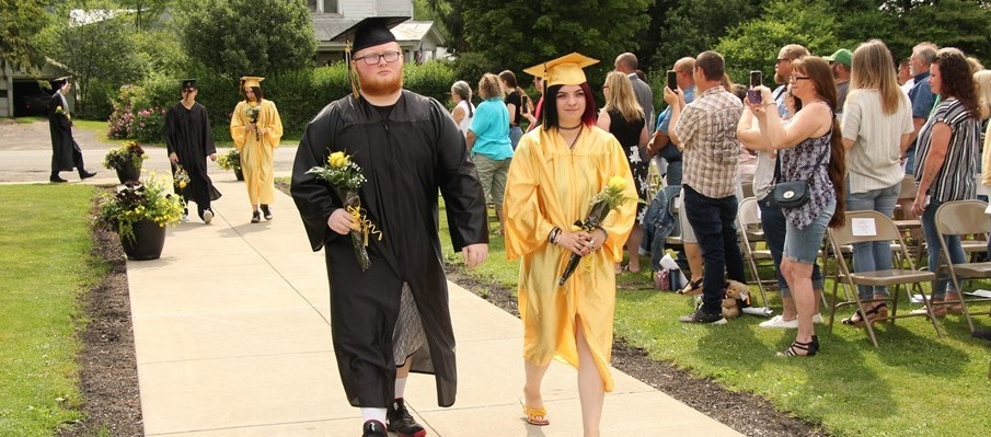 Two graduating seniors in gold and black caps and gowns process down a sidewalk with family and friends looking on