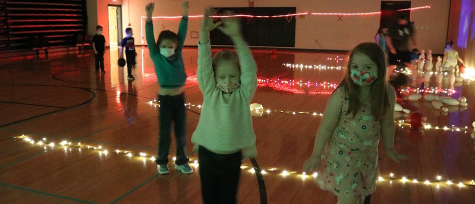 3 elementary school girls dance in darkened gym lit by rows of small white lights showing pretend bowling lanes