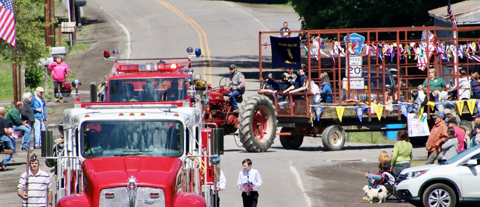 a parade with fire trucks and a tractor pulling a float on a hay wagon that celebrates agriculture