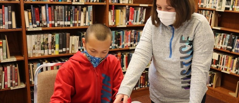 a girl in a school library points to the paper a boy is working on while seated at a table with colored pencils