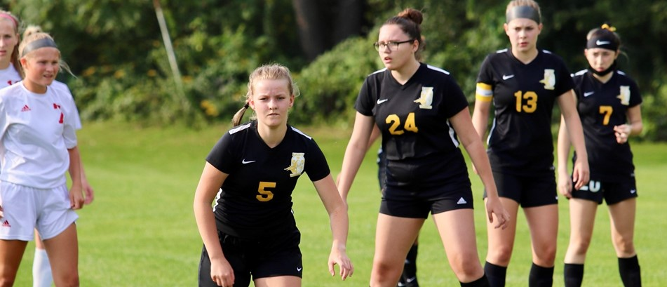 girls varsity soccer athletes in black uniforms stand poised on a soccer field, ready to run