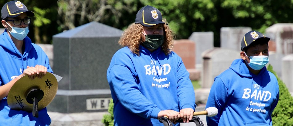 3 male students in blue band sweatshirts and masks pause with their percussion instruments in a cemetery for a Memorial Day performance