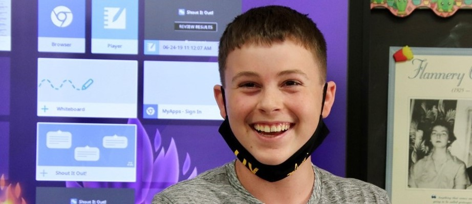 a smiling boy in a grey shirt, with a mask pulled under his chin, stands in front of a bulletin board