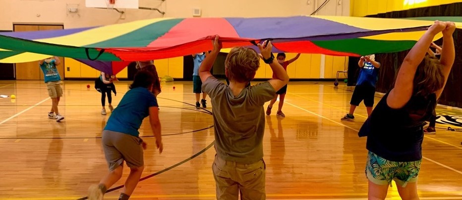 elementary students in a gym hold up rainbow colored parachute fabric while a boy runs underneath