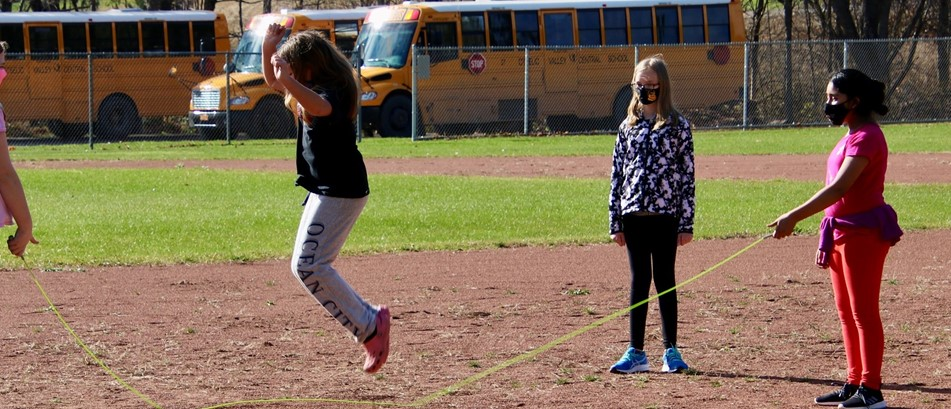 Girls in masks jump rope on a baseball field while one watches
