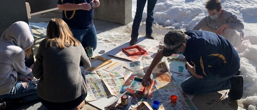 Students kneel outdoors on sidewalk cleared of snow while spraypainting picture frames arranged on newspaper