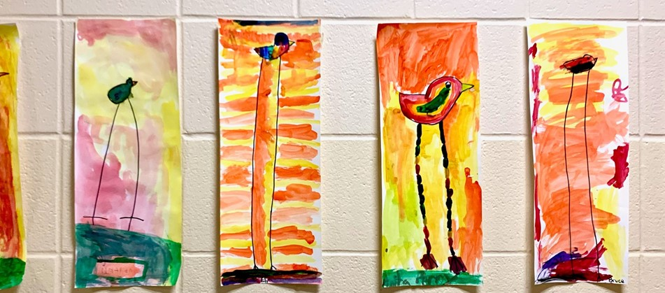 student paintings show long legged birds standing on grass with orange and yellow skies in the background