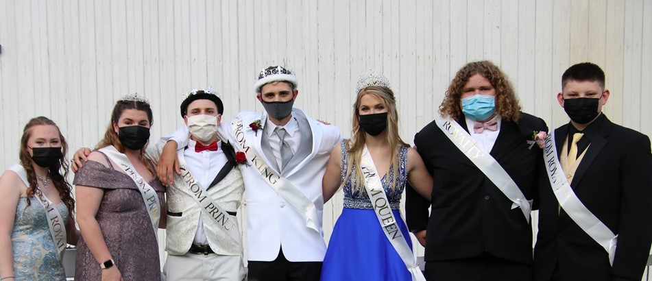 teenage girls and boys in a line wear prom attire, crowns, sashes, and masks